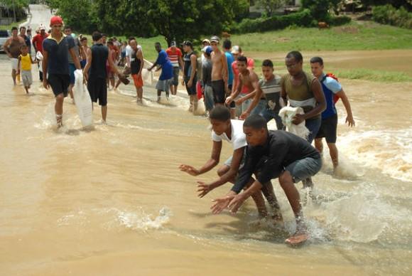 Pobladores del municipio de Sagua de Tánamo, disfrutan de la pesca aprovechando la crecida del río por intensas lluvias, provocadas por la tormenta tropical Isaac, a su paso por la provincia de Holguín, Cuba, el 26 de agosto de 2012. AIN FOTO/Juan Pablo CARRERAS/