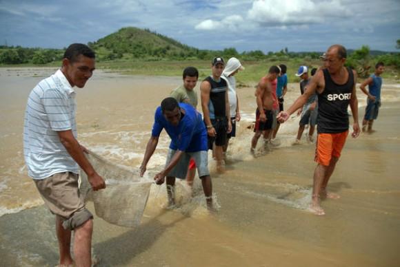 Pobladores del municipio de Sagua de Tánamo, disfrutan de la pesca aprovechando la crecida del río por intensas lluvias, provocadas por la tormenta tropical Isaac, a su paso por la provincia de Holguín, Cuba, el 26 de agosto de 2012. AIN FOTO/Juan Pablo CARRERAS