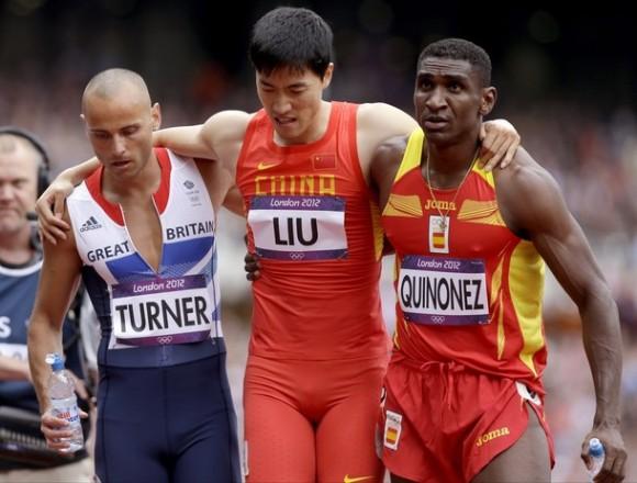 Liu Xiang es ayudado por el británico Andrew Turner, a la izquierda, y el español Jackson Quiñónez después de su caída en la carrera. Foto: AP Photo/Anja Niedringhaus.