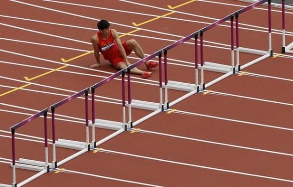 Liu Xiang se sostiene la pierna después de sufrir una lesión en la carrera de los 110 metros con vallas. Foto: Reuters/Stefan Wermuth.