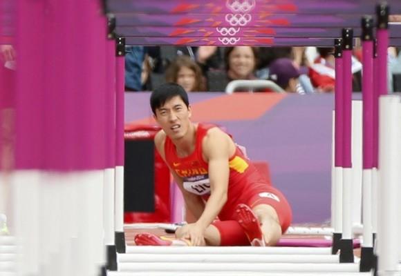 Liu Xiang se sienta en la pista después de caer en la primera valla en el heat de los 110 metros con vallas en en el Estadio Olímpico de Londres el 7 de agosto de 2012. Foto: Reuters/Lucy Nicholson.