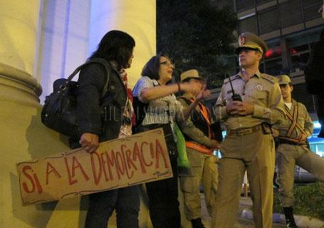 """La activista de Derechos Humanos, Line Bareiro, explicando a los policías el derecho de la ciudadanía a la libre manifestación. Foto: Página de """"HK Justiciera"""" en Facebook."""