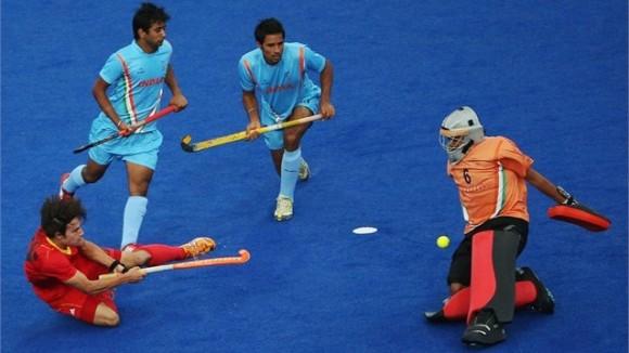 El portero indio Bharat Kumar Chetri para un disparo de Thomas Briels de Bélgica en Hockey sobre Césped