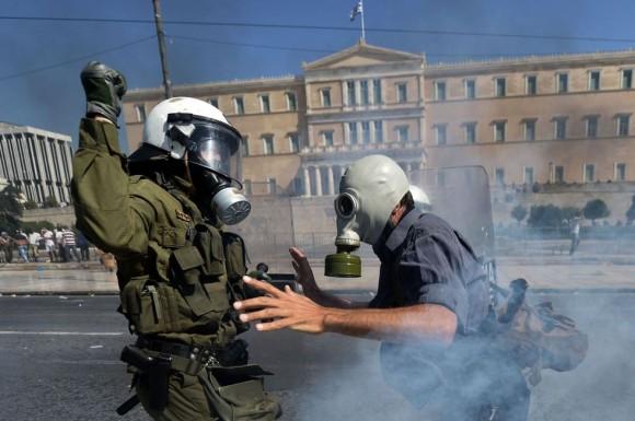 Un manifestante se enfrenta a un policía antidisturbios frente al Parlamento. ARIS MESSINIS (AFP)