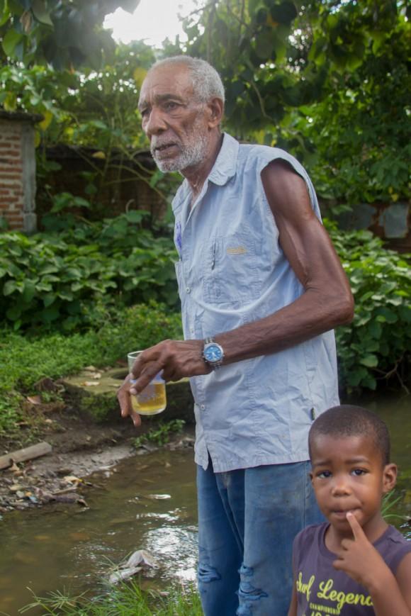 El vecino que cuenta que esta cañería de agua albañal está rota hace siete años. Cuando llueve el agua infectada penetra en las casas. En las calles la superficie es resbalosa y a menudo hay accidentes. Los vecinos no pueden hacer nada más que contarlo. Foto: Jorge Ramírez.