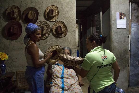 María Regla escoge uno de sus sombreros para enviarlo como obsequio al trovador. Se lo entrega a una miembro de su equipo. Foto: Jorge Ramírez.