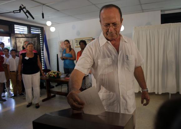 Santiago González Carrera, miembro de la mesa electoral mientras deposita el voto de Fidel Castro. Foto Cubadebate
