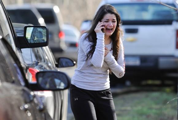 Una mujer, hermana de una profesora, habla desesperada a las puertas del colegio de Newtown. Foto: AP.