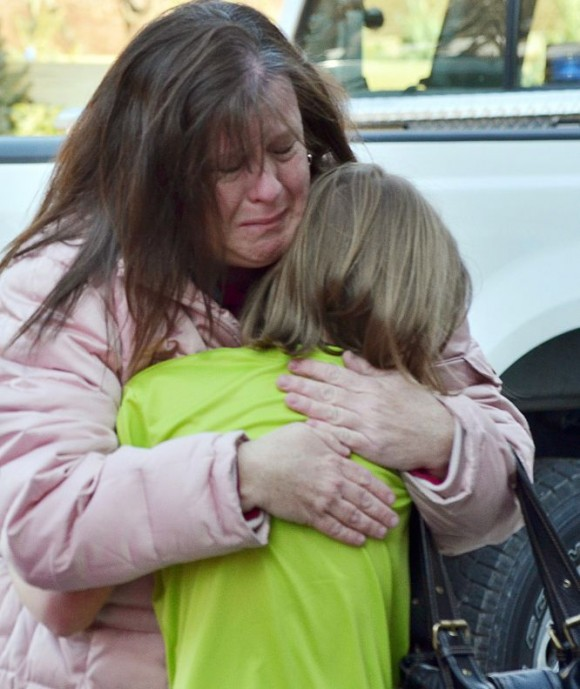 Una madre abraza a su hija a las puertas del colegio Sandy Hook. Foto: AP.
