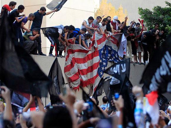 El Cairo: Egipcios airados destrozan una bandera en la Embajada norteamericana como represalia por una película que ofendía a Mahoma. Foto: REUTERS/MOHAMED ABD EL GHANY.