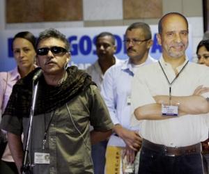 """Jesús Santrich, miembro de la delegación de las FARC, junto a una gigantografia del ausente Comandante """"Simón Trinidad"""". Foto: Ismael Francisco/Cubadebate."""
