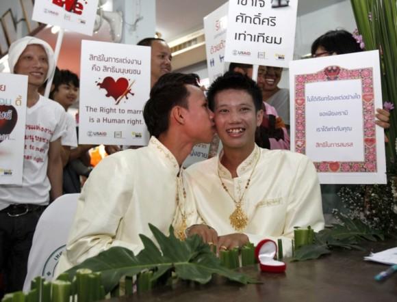 El tailandés Jedwarut Boonpan, besa a su pareja, Nattapol Panumong, mientras sus amigos sujetan pancartas pidiendo el derecho a las parejas homosexuales a casarse, durante su boda celebrada el día de San Valentín, en la provincia de Chiang Mai, al norte de Tailandia. Foto: Pongmanat Tasiri / EFE