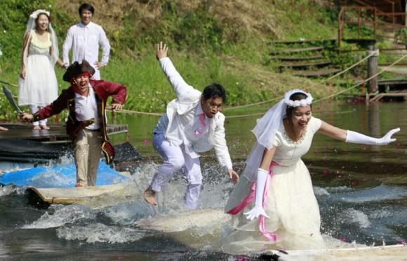 Una pareja tailandesa recién casada corren sobre el agua perseguidos por un hombre disfrazado de pirata durante una boda desafío de aventura, en el distrito Nadi de la provincia de Prachinburi, en Tailandia. Foto: Natita Phodee / EFE