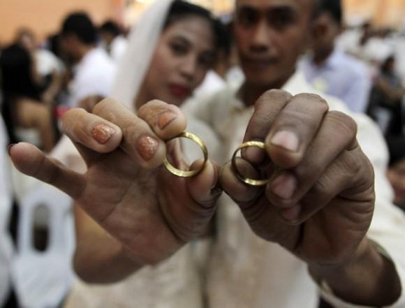Los recién casados Brandon Balinue (der) y Juie Anne muestran sus anillos durante una boda conjunta en el día de San Valentín, en el ayuntamiento de Taguig, al sur de Manila, en Filipinas. Foto: Francis Malasig / EFE