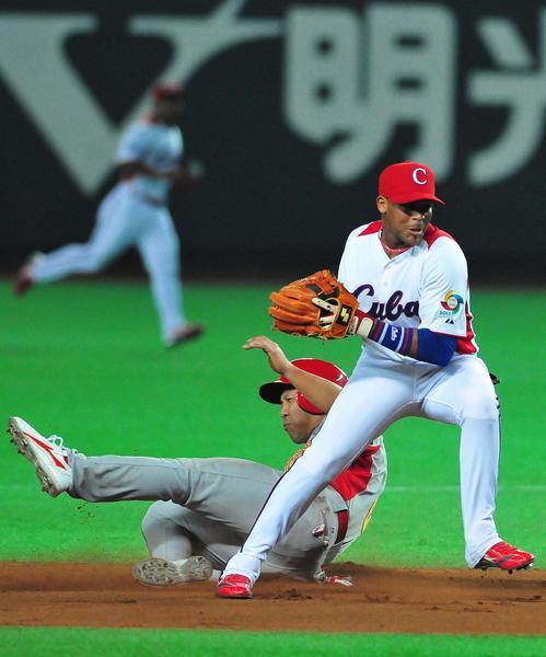 El pelotero cubano José Miguel Fernández (I) en el juego contra China, donde Cuba venció doce carreras por cero y aseguró su presencia en la segunda ronda del III Clásico Mundial de Béisbol, en la ciudad de Fukuoka, en Japón, el 3 de marzo de 2013. AIN FOTO POOL/Ricardo LÓPEZ HEVIA/Periódico Granma