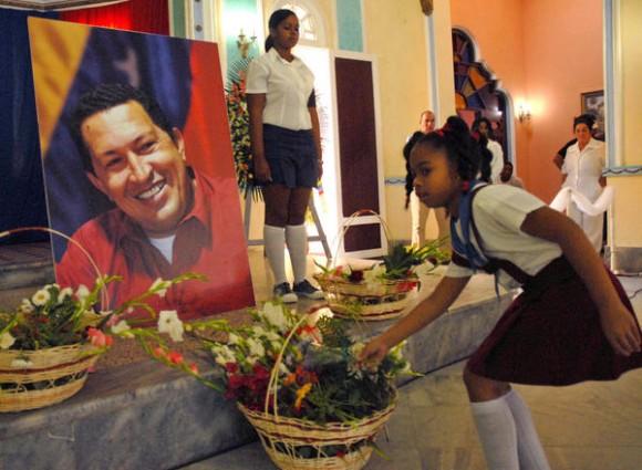 Pionera pinareña deposita flores durante el homenaje póstumo al Presidente venezolano Hugo Rafael Chávez, en la sala principal de un Palacio de la ciudad de Pinar del Río, el 07 de marzo de 2013.   AIN FOTO/Abel PADR?N PADILLA