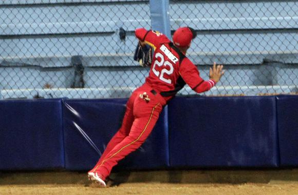 Yadier Hernández impacta con la cerca del latino al capturar un batazo. Foto: Ismael Francisco/Cubadebate.