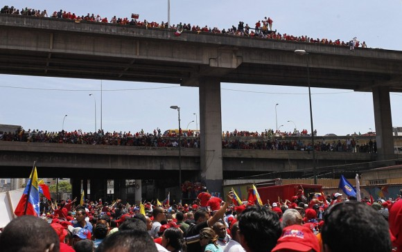 Supporters of deceased Venezuelan leader Hugo Chavez gather to watch as his coffin is driven through the streets of Caracas