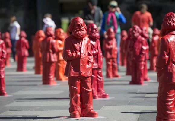 Las figuras representan a Marx con su abrigo de invierno, con la mano derecha bajo el corazón, como si quisiera sacar su reloj de bolsillo o su monedero.