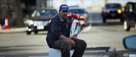 A man selling Mother's Day flowers sits in the median of a street in Cambridge
