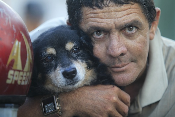 Popy, a 14-year-old dog, posses for a photo with his owner Abel in Havana