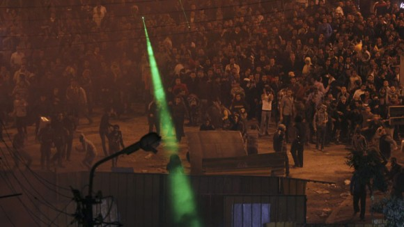 Anti-Mursi protesters throw stones and shine laser pointers at supporters of Egyptian President Mursi, outside the presidential palace in Cairo