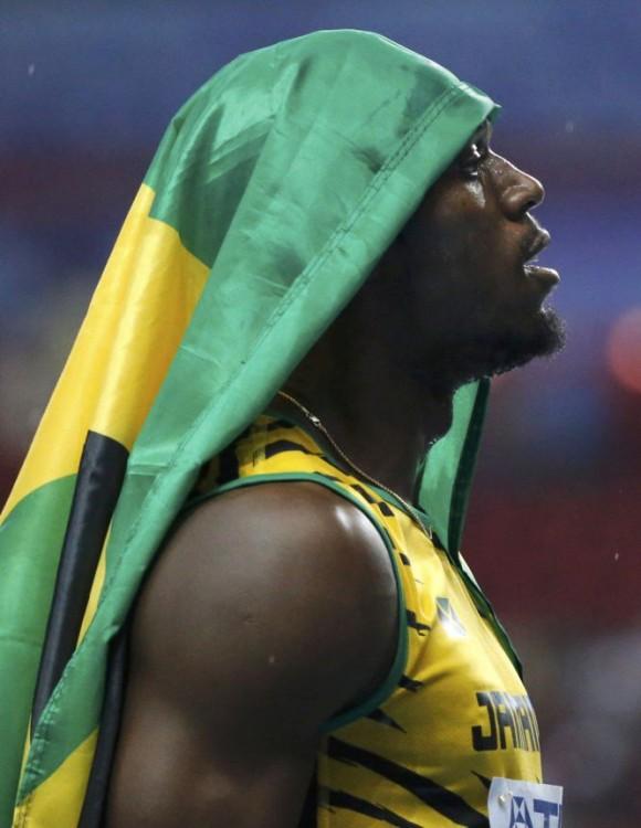 Bolt cubre su cabeza con una bandera de Jamaica.FABRIZIO BENSCH (REUTERS