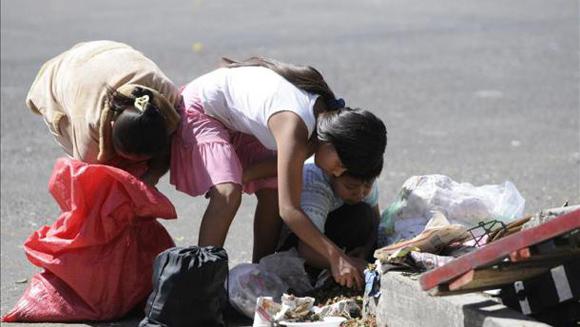 Niños guatemaltecos buscan alimentos entre la basura.