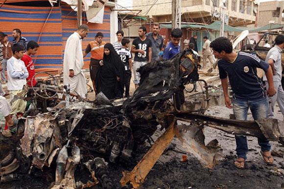 Varias personas miran los restos de un coche bomba que explotó en el este de Bagdad, este miércoles. Foto: AP.