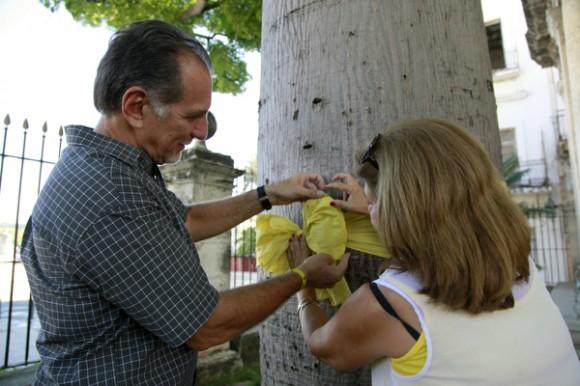 René González y Olga Salanueva atan cinta amarilla a la ceiba de El Templete. Foto: Roberto Chile/ Cubadebate