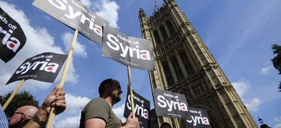 Numerosos manifestantes muestran pancartas durante una concentración contra una posible intervención militar en Siria, a las puertas del Parlamento británico en Londres.