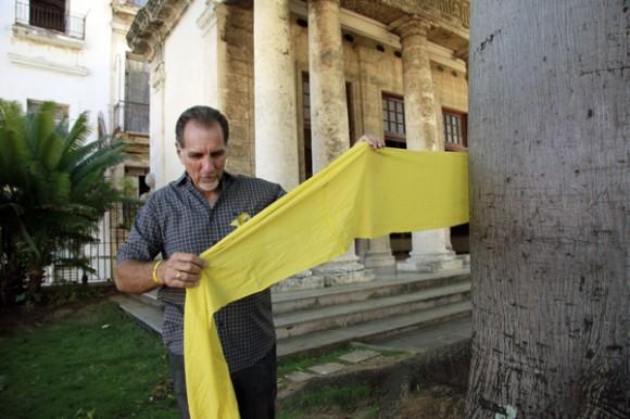 René González ata una cinta amarilla a la ceiba de El Templete, en La Habana Vieja. Foto: Roberto Chile/Cubadebate