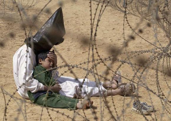 Un iraquí reconforta a su hijo en un centro de prisioneros de An Najaf, Irak, durante la guerra