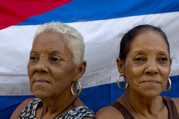 Las hermanas gemelas Fe Fernández, (izq) y Esperanza, de 65 años, posan frente a una bandera cubana en la calle donde viven en La Habana.