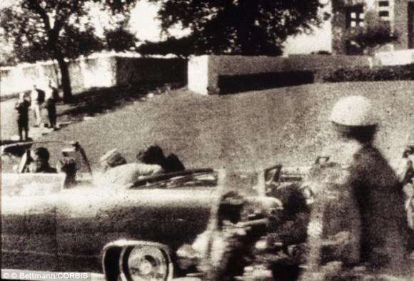 El primer disparo es desviado por un árbol y rebota en el cemento llegando a herir al testigo James Tague. 3,5 segundos después se produce el segundo disparo que llega a Kennedy por detrás y sale por su garganta,3 hiriendo también al gobernador de Texas, John Connally. El presidente deja de saludar al público y su esposa tira de él para recostarlo sobre el asiento. El tercer disparo ocurre 8,4 segundos después del primer disparo, justo cuando el auto pasa al frente de la pergola de hormigón. Cuando el tercer disparo impacta de lleno en el occipital derecho de la cabeza de Kennedy, Jackie Kennedy, se abalanza a la parte trasera del auto, donde recoge una sección del cráneo del presidente. Un ciudadano de nombre Abraham Zapruder, que filmaba la comitiva presidencial, logró captar en su película el momento en que Kennedy es alcanzado por los disparos. Esta película es parte del material que la Comisión Warren utilizó en su investigación del asesinato.