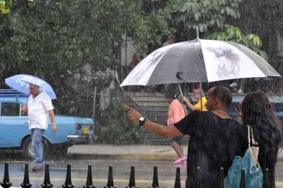Desde la noche del martes no cesa de llover en la capital cubana por la entrada de un frente frio. Una pareja se protege de la lluvia en la calle 23, en La Habana, durante un cambio de tiempo en el occidente de Cuba, el 13 de noviembre de 2013.  AIN FOTO/Roberto MOREJÓN RODRÍGUEZ/