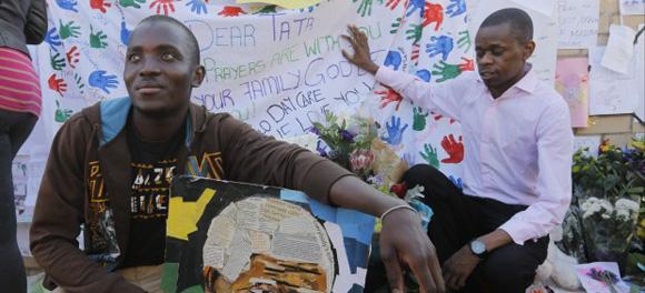 Un hombre muestra un retrato del expresidente sudafricano Nelson Mandela a las puertas del hospital.