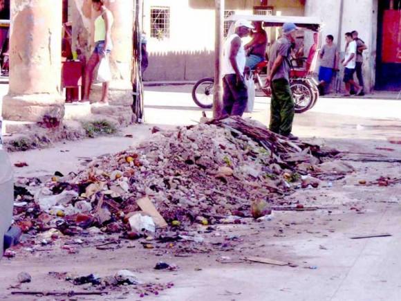 """Un lector de Cubadebate se llegó a donde estaba la """"laguna verde"""" en la calle Egido y Corrales, reflejada hace semanas en esta sección. Por suerte, ya no está la laguna, pues a raíz del reportaje se movilizaron y taparon el hueco, dice el lector.. Quedó bastante bueno, pero ahora se puede notar,  EN EL MISMO LUGAR DE LA LAGUNA, un montón de escombros, y un basurero putrefacto. La ironía es que está en el mismo lugar, ni más, ni menos. Se ha cambiado la putrefacción de la laguna por la inmundicia del basurero. Foto: Yoniesky Rodríguez, Lector de Cubadebate"""