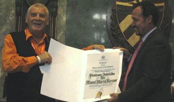 Martín Serrano recibió hoy de manos del Dr. Raúl Garcés, decano de la Facultad de Comunicación de la UH, el diploma que le confiere la categoría docente especial de Profesor Invitado de la UH. Foto: Fernando Medina/ ICOM2013.com