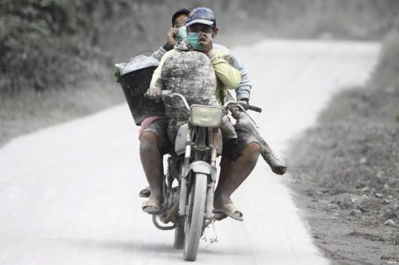 Agricultores recorren en moto los alrededores del volcán. Foto: AFP.
