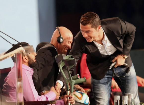 Ronaldo le da la mano a un joven minusválido de Emiratos Árabes Unidos durante Conferencia. Foto: EFE