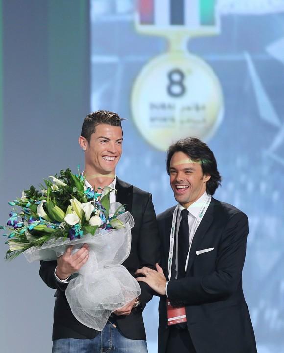 Tommaso Bendoni, gerente general de Dubai Sports Channel, le entrega un ramo de flores al delantero del Real Madrid durante la primera sesión de la octava edición de la Conferencia Internacional del Deporte en Dubai, Emiratos Árabes Unidos. Foto: EFE