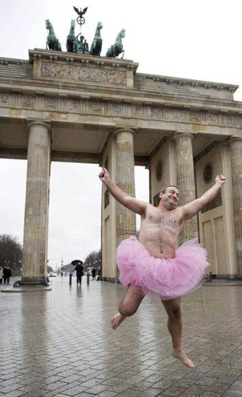 """Bob Carey salta con un tutú rosa delante de la Puerta de Brandemburgo, en Berlín, Alemania. Bob y Linda Carey son los fundadores del """"Tutu Project"""", una iniciativa destinada a tomar conciencia sobre el cáncer de mama mediante retratos en los que posan con esta prenda de ballet. Foto: BERND VON JUTRCZENKA (EFE)"""