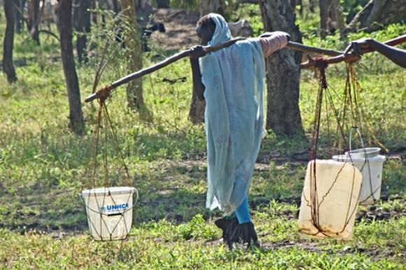 Una refugiada de Sudán recorre un largo camino desde el punto de abastecimiento de agua más cercano a su alojamiento temporal, cargada con recipientes de plástico llenos de agua. El CICR está mejorando la red de abastecimiento de agua para hacer más liviano su trabajo y el de tantas otras.
