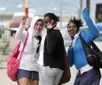 Jóvenes saludan mientras pasean bajo las temperaturas mínimas provocadas por el primer frente frio del año en La Habana, Cuba, el 7 de enero de 2014. AIN FOTO/Roberto MOREJÓN RODRÍGUEZ/oca