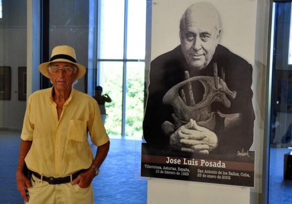 Eugenio Posada, junto a la imagen de su hermano. Foto: Roberto Garaycoa / Cubadebate.