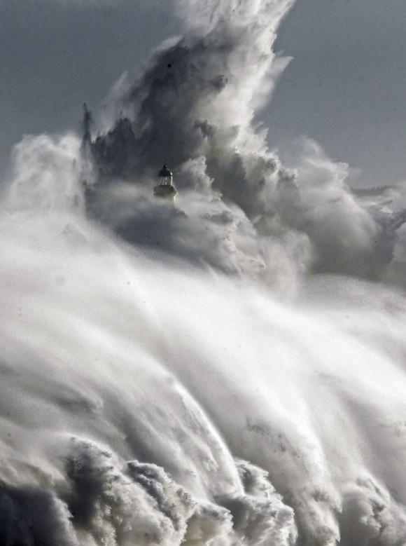 Una ola rompe frente a la isla de Mouro en la bocana del puerto de Santander. Foto: EFE
