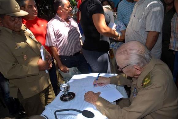 """Guillermo García Frías (Derecha), escribe la dedicatoria de un ejemplar de su libro """"""""El último combate"""". Foto: AIN"""