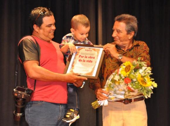 El destacado fotorreportero Ismael González (D), recibe de manos de su hijo Ismael Francisco González, también fotorreportero en Cubadebate, el premio provincial de periodismo  Por la obra de la vida, que lleva el nombre del colega Rubén Castillo Ramos, durante el acto celebrado en la jornada por el Día de la Prensa, en la ciudad de Bayamo, en Granma, el 20 de marzo de 2014.    AIN FOTO/Marcelino VÁZQUEZ HERNÁNDEZ