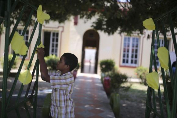Un niño coloca flores amarillas de papel en la verja de un colegio que funciona en el edificio que acogió la escuela donde el Premio Nobel de Literatura Gabriel García Márquez hizo los estudios primarios, en su pueblo natal de Aracataca, en Colombia. Lunes 21 de abril de 2014. AP Photo/Ricardo Mazalan